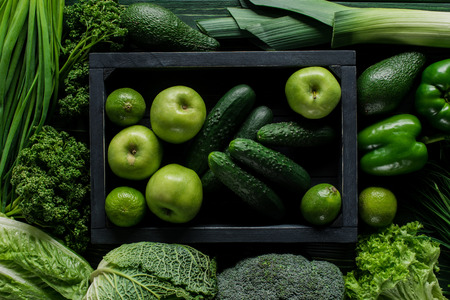 Top view of apples and cucumbers in wooden box between green vegetables, healthy eating concept 版權商用圖片