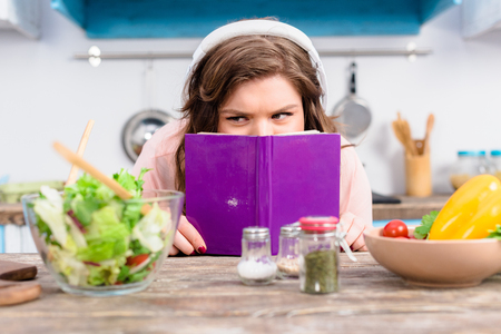 Obscured view of overweight woman in headphones hiding behind cookery book at table with fresh salad in kitchen at home