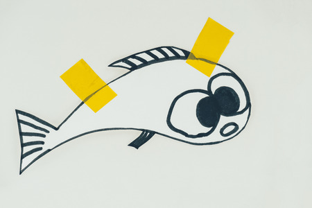 Close up view of hand drawn fish with sticky tapes isolated on grey background, April fools day holiday concept