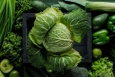 Elevated view of green savoy cabbage in wooden box between vegetables, healthy eating concept