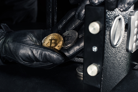 Thief hand stealing golden bitcoin from safe