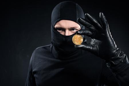 Man in black balaclava holding golden bitcoin