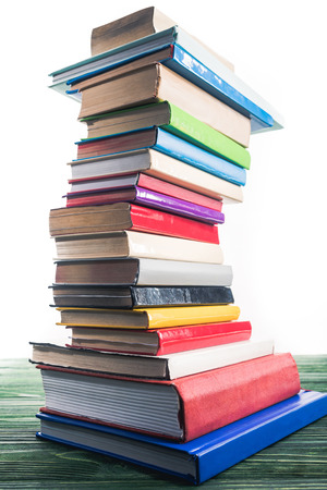 High bent tower of stacked books on wooden table Archivio Fotografico
