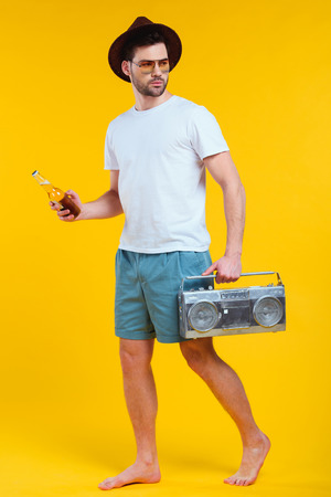 Young barefoot man in shorts holding tape recorder and bottle of summer drink isolated on yellow background