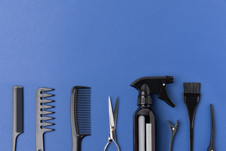 Flat lay with black hairdressing tools in row, isolated on blue background Фото со стока - 110886663