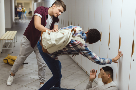 Schoolboys being bullied in school corridor by their classmate