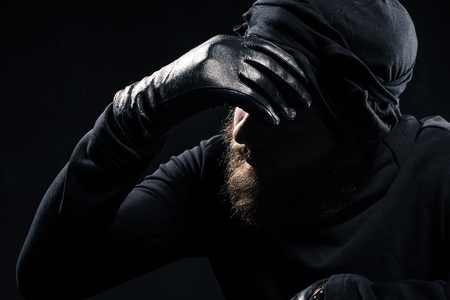Robber in balaclava leaning his head on hand Stock Photo