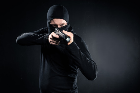 Robber in balaclava aiming with gun on black background Stock Photo