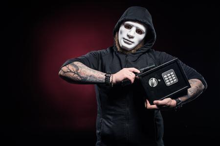 Burglar in mask holding gun and locked safe