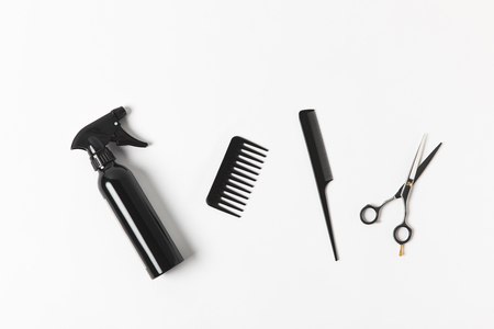 Top view of spray bottle, combs and scissors, on white background