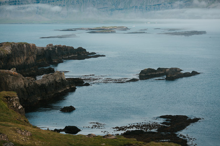 Beautiful rocky coast and water of fjord in Iceland