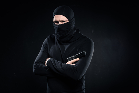 Thief in black balaclava holding gun in folded arms on black background