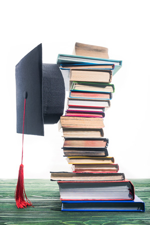 Graduation cap fixed between stacked books Imagens