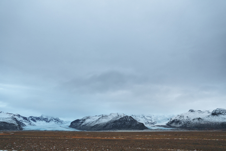 Beautiful scenic view of snow-covered rocky mountains and cloudy sky, Iceland