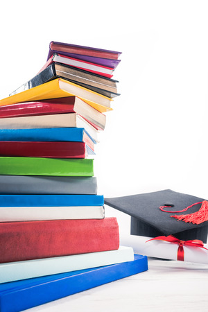 Graduation hat and diploma with red ribbon by books on table
