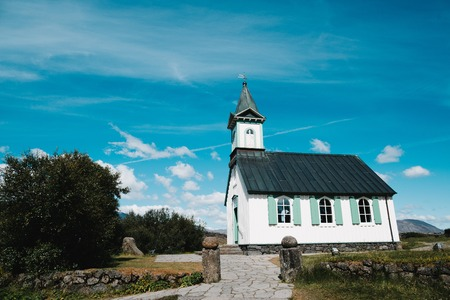 Architecture of beautiful traditional church and old stone wall at sunny day, Pingvallakirkja, Iceland Stok Fotoğraf