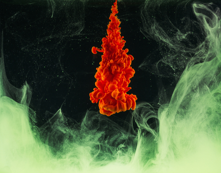 Bright abstract orange ink explosion on black background Stock Photo