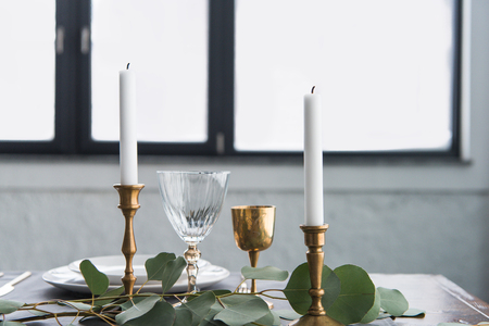Close up view of rustic table arrangement with wine glasses, eucalyptus, candles in vintage candle holders and empty plates