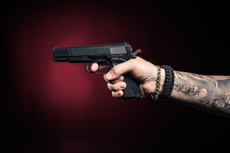 Close-up view of male hand aiming with gun Stock Photo