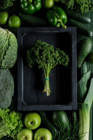 Top view of bunch of parsley in wooden box between green vegetables, healthy eating concept