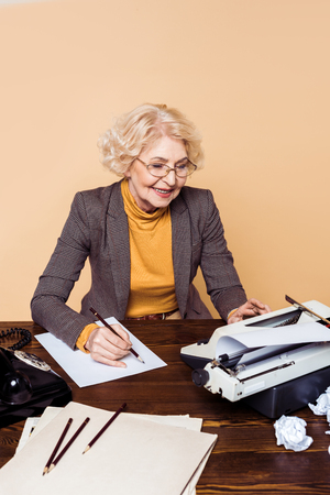 Smiling stylish senior woman in eyeglasses writing on paper