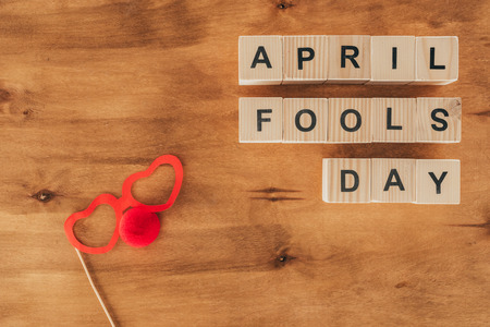 Top view of arranged wooden cubes in April fools day lettering with party eyeglasses and clown nose on wooden tabletop, 1 April holiday concept Stock Photo