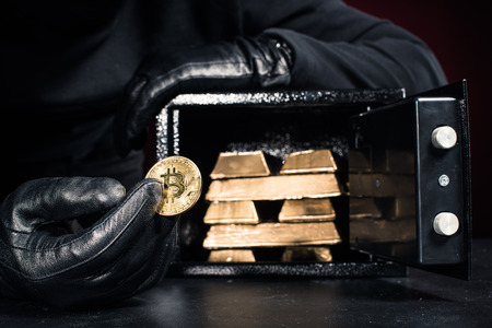 Cropped view of thief stealing gold bullions and bitcoin from safe