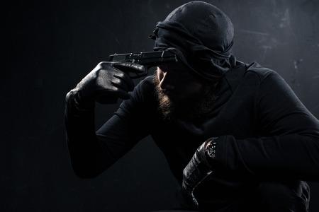 Burglar in balaclava scratching his head with gun