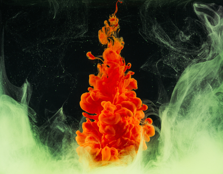 Close-up view of bright abstract orange paint explosion on black background