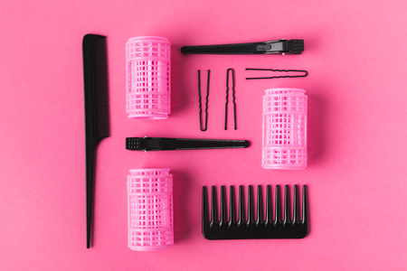 Flat lay with curlers, combs and hairclips, on pink background Фото со стока
