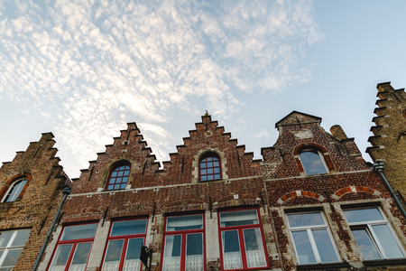 Low angle view of beautiful traditional houses against blue sky, Brugge, Belgium