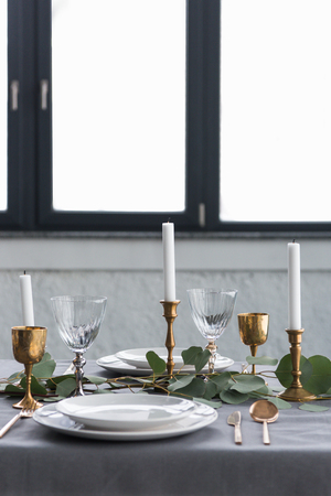 Close up view of rustic table setting with eucalyptus, vintage tarnished cutlery, candles in candle holders and empty plates Stock Photo - 110887444
