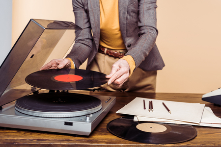 Cropped shot of woman turning on vinyl record player