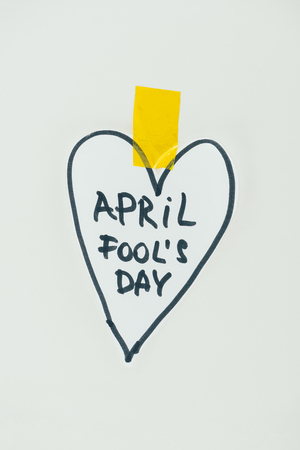 Close up view of hand drawn heart and April fools day lettering isolated on grey background, April fools day concept