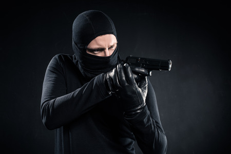 Burglar in balaclava aiming with gun on black background