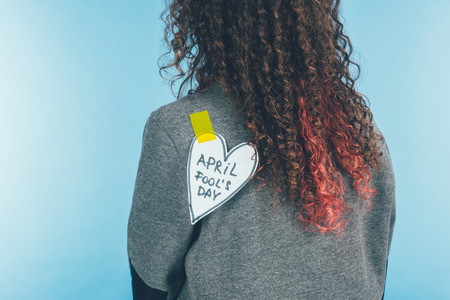 Back view of woman with heart on sticky tape with April fools day lettering on back, April fools day concept