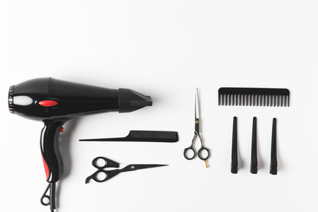 Flat lay with hairdryer and hairdressing tools, on white background