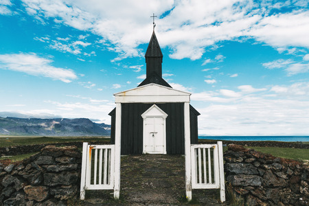 White gates and stone wall at entering to small church in Budir, Snaefellsnes peninsula, Iceland