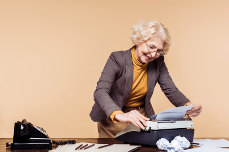 Smiling senior woman using typewriter at table with rotary phone Stock fotó