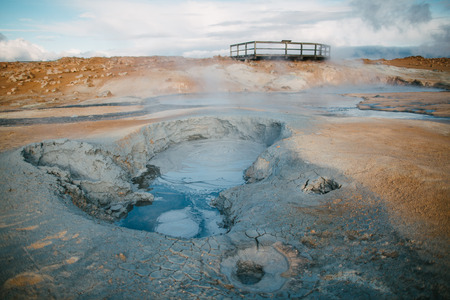 Beautiful scenic view of geothermal hot springs with steam and wooden bridge behind, Iceland 写真素材