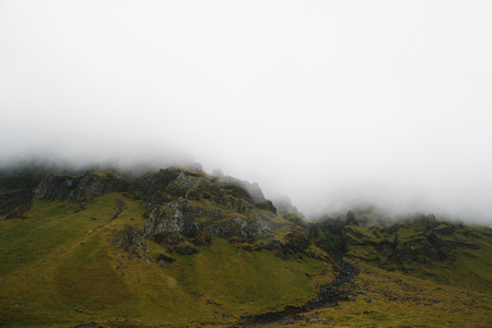 Majestic rocky hills covered with green moss in fog, Iceland 写真素材