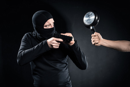 Thief with gun being hit by frying pan