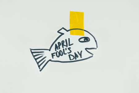 Close up view of hand drawn fish with April fools day lettering and sticky tape isolated on grey background, April fools day holiday concept