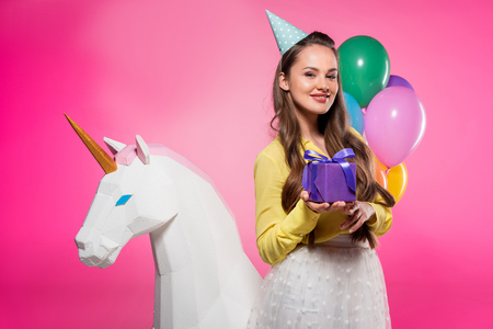 Attractive woman with party hat and gift box isolated on pink background
