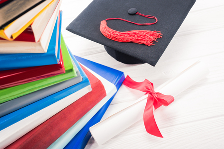 Graduation hat and diploma on white table by stacked books