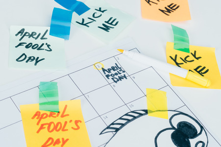 Close up view of calendar with April fools day lettering isolated on grey surface, April fools day holiday concept
