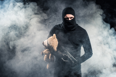 Criminal in balaclava holding gun and teddy bear in clouds of smoke
