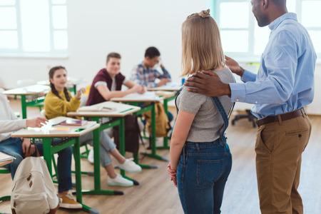 Insegnante afroamericano che presenta una nuova ragazza ai compagni di classe multiculturali