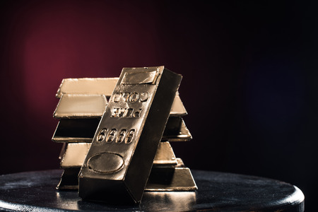 Stack of golden ingots on table against red background Stock Photo