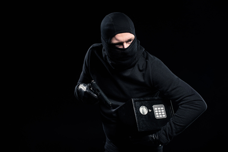 Burglar in balaclava holding gun and locked safe box